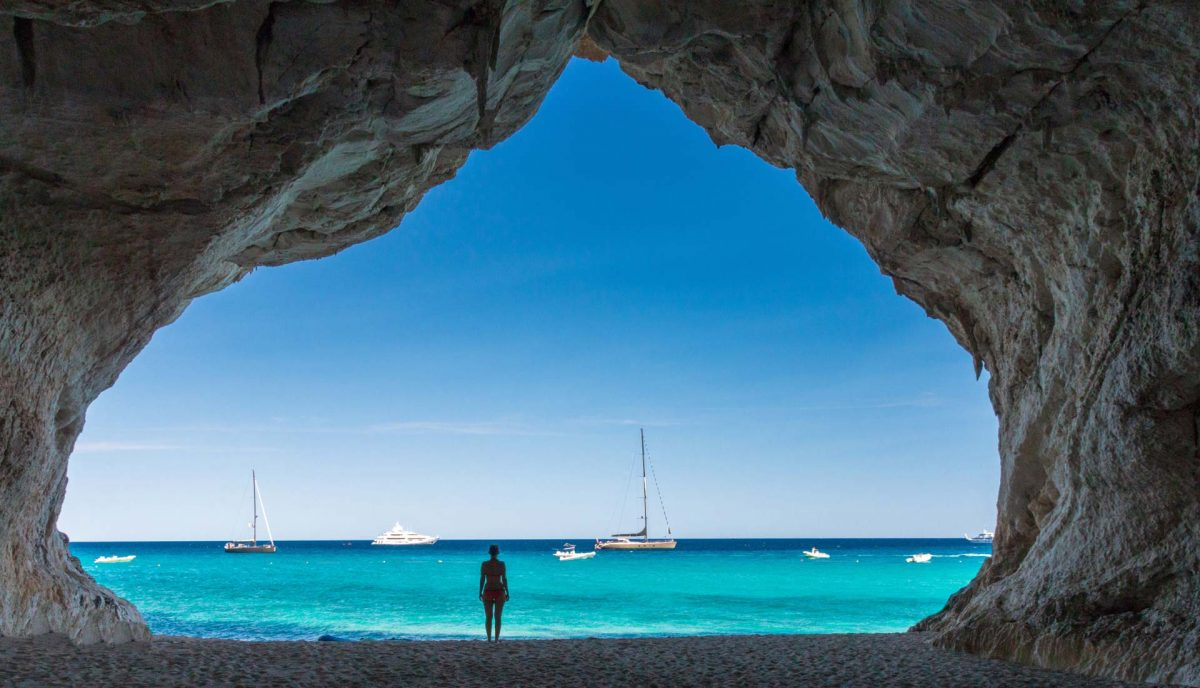 Woman standing in cave staring out to sea and boats on the horizon